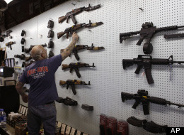 In this Tuesday Feb. 5, 2013 photo, gun dealer Mel Bernstein takes down an AK-47 assault rifle from a sales rack at his own Dragonman's shooting range and gun store, east of Colorado Springs, Colo. (AP Photo/Brennan Linsley)