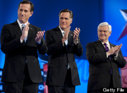 Republican presidential candidates Rick Santorum, Mitt Romney and Newt Gingrich applaud the arrival of Ron Paul to the debate hall on Feb. 22, 2012 in Mesa, Ariz. (DON EMMERT/AFP/Getty Images)