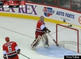 Hurricanes goalie Dan Ellis removes the puck from his net after Devils goalie Martin Brodeur scores on an empty net after an errant pass from Jordan Staal.