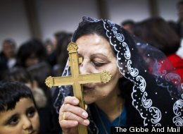 An Iraqi-Canadian kisses the cross during mass at the Our Lady of Good Counsel Church in Surrey December 12, 2010. New immigrants to Canada, many who look to their faith for comfort in a new country, are changing the country's religious makeup, according to data released from the 2011 National Household Survey. (John Lehmann/The Globe and Mail)