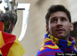 Barcelona's Argentinian forward Lionel Messi (R) reacts as he and his teammates parade on a bus through a crowd of supporters celebrating in the streets of Barcelona on May 13, 2013, two days after their team won the Spanish league. (Photo credit should read LLUIS GENE/AFP/Getty Images)