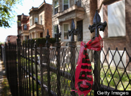 Crime scene tape hangs from a fence near the location where 21-year-old Ronald Baskin was shot and killed Sunday afternoon on May 13, 2013 in Chicago. Violence surged again on Chicago's streets overnight Wednesday. (Photo by Scott Olson/Getty Images)