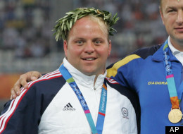 FILE - In this Aug. 20, 2004, file photo, shot put medalists of the 2004 Olympic Games, from left, silver medalist Adam Nelson, of the United States, silver, gold medalist Yuriy Bilonog, Ukraine, and bronze medalist Joachim Olseno Denmark pose on the podium after the presentation ceremony in the Olympic Stadium in Athens.