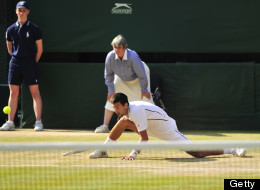 Novak Djokovic slides during a point with Andy Murray in their men's singles final of the 2013 Wimbledon Championships on July 7, 2013.