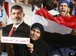 A supporter of Egypt's ousted President Mohammed Morsi raises his picture with a slogan