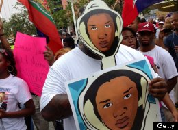 Aqua Etefia attends a 'Justice for Trayvon' rally, holding Trayvon Martin signs, at the Wilkie D. Ferguson, Jr. United States Federal Courthouse in Miami, Florida, Saturday July 20, 2013. Trayvon's father, Tracy Martin, was on hand to speak to a large crowd of people unhappy with the verdict. (Emily Michot/Miami Herald/MCT via Getty Images)