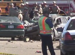 Authorities gather around the wreckage of a mangled car hit by the driver of a stolen truck that left six dead in Hidalgo County, Texas