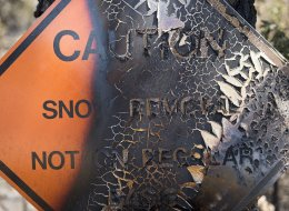 Paint peels from a sign burned in the Rim Fire in the Stanislaus National Forest along Highway 120 near Yosemite National Park, California, Monday, August 26, 2013. (Paul Kitagaki Jr./Sacramento Bee/MCT via Getty Images)