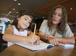 Roxana A. Soto (derecha), co-autora del libro 'Bilingual is Better', enseña a su hija Vanessa, de 6 años de edad, cómo escribir en español.