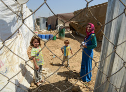ZAHLE, LEBANON - SEPTEMBER 5, 2013: A Syrian refugee woman seen with her children behind the fence while holding medication after visiting the clinic in Dalhamieh settlement in Bekaa valley in Zahle on September 5, 2013. This health care is sponsored by UNICEF  and executed by Lebanese non governmental organization (NGO) called Beyond Association. (Photo by Kaveh Kazemi/Getty Images)