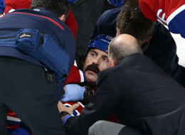 Montreal Canadiens right wing George Parros (15) is treated by medical staff after Parros hit his head on the ice during a fight with Toronto Maple Leafs right wing Colton Orr during third period National Hockey League action Tuesday, October 1, 2013 in Montreal.THE CANADIAN PRESS/Ryan Remiorz