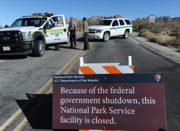 U.S. Park Rangers stand at the closed gate to Joshua Tree National Park in Joshua Tree, Calif., on Oct. 2, the second day of the government shutdown. (ROBYN BECK/AFP/Getty Images)
