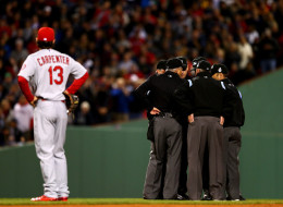 Umpires discuss a play at second base involving Pete Kozma #38 of the St. Louis Cardinals and Dustin Pedroia #15 of the Boston Red Sox in the first inning of Game One of the 2013 World Series at Fenway Park on October 23, 2013 in Boston, Massachusetts.