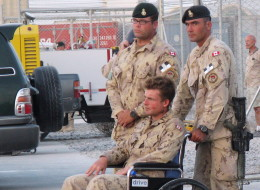 Pte. Glen Kirkland, in wheelchair, one of five soldiers injured in a direct fire explosion, attends a ramp ceremony for fallen comrades Cpl. Andrew Grenon, Cpl. Mike Seggie and Pte. Chad Horn, in Kandahar, Afghanistan, Thursday Sept. 4, 2008. Gravely injured troops who want to remain uniform are being booted from the military before they qualify for their pensions, despite assurances to the contrary from the Harper government. (THE CANADIAN PRESS/Tobi Cohen)
