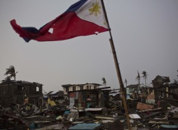 A flag of the Philippines flies over a destroyed neighborhood in Tacloban, Philippines on Friday Nov. 22, 2013. (AP Photo/David Guttenfelder)