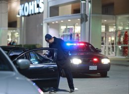 A detective investigates the scene of a police-involved shooting outside Kohl's department store on Weber Road in Romeoville, Ill., Nov. 28, 2013. A theft attempt by two or more suspects resulted in police action and the shooting scene outside the store. (John J. Kim/Chicago Tribune/MCT via Getty Images)