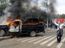 A protester stands in front of a burning police vehicle set afire by protesters, near Cairo University.