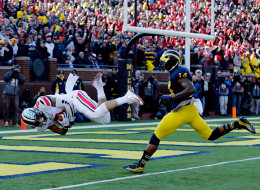 Wide receiver Devin Smith #9 of the Ohio State Buckeyes scores a touchdown in the first quarter as safety Josh Furman #14 of the Michigan Wolverines defends during a game at Michigan Stadium on November 30, 2013 in Ann Arbor, Michigan.  (Photo by Gregory Shamus/Getty Images)