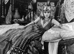 Theda Bara sits on a bed of cushions in a scene from the film 'Cleopatra', 1917. (Photo by Fox/Getty Images)