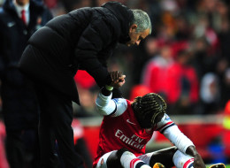 ose Mourinho manager of Chelsea helps Bacary Sagna of Arsenal to his feet during the Barclays Premier League match between Arsenal and Chelsea at Emirates Stadium on December 23, 2013 in London, England.