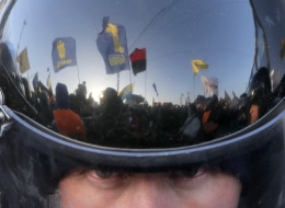 A thousand-strong pro-European Union rally is reflected in the surface of a riot police officer's helmet as he guards the way to Ukrainian President Viktor Yanukovych's country residence of Mezhygirya outside Kiev, Ukraine, Sunday, Dec. 29, 2013. (AP Photo/Efrem Lukatsky)