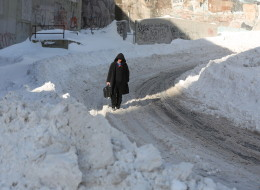 A man walks down a snow-covered road after a winter storm hit St.John's. N.L., Sunday, Jan.5, 2014. THE CANADIAN PRESS/Paul Daly