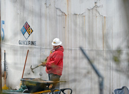 An unidentified worker at Freedom Industries shovels NAPA premium oil absorbent on Jan. 10, 2014  in Charleston, W.Va. West Virginia American Water determined Thursday MCHM chemical had