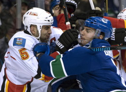 Vancouver Canucks left wing Alex Burrows (14) wrestles with Calgary Flames defenscman Mark Giordano (5) during the first period of NHL action in Vancouver on Saturday.