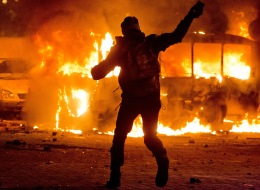 A protester throws a stone towards a burning police bus in front of him, during clashes with police, in central Kiev, Ukraine, Sunday, Jan. 19, 2014. (AP Photo/Evgeny Feldman)