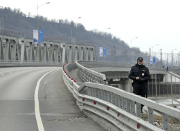 A police officer stands guard along the road between the mountain and coastal venues for the 2014 Winter Olympics, Wednesday, Feb. 5, 2014, outside of Sochi, Russia. (AP Photo/Charlie Riedel)