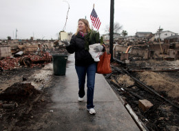 NEW YORK, NY - DECEMBER 07:  Sheila Scandole recovers plants and an American flag for her boyfriend in the hard hit Breezy Point neighborhood on December 7, 2012 in the Queens borough of New York City. Breezy Point, home to many New York City firefighters and police, lost 111 homes in a fast moving fire during Superstorm Sandy with many more homes severely damaged from flooding.  (Photo by Mario Tama/Getty Images)