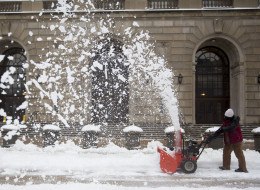 A worker uses a snow blower outside the Internal Revenue Service in Washington, D.C. on Thursday, Feb. 13, 2014. (Andrew Harrer/Bloomberg via Getty Images)