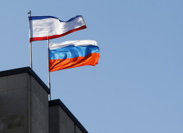 SIMFEROPOL, UKRAINE - MARCH 15:  Russian flag held is seen on the Crimean parliament building before the Crimean referendum in Simferopol on March 15, 2014. (Photo by Bulent Doruk/Anadolu Agency/Getty Images)