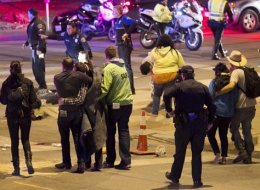 People walk away after the accident on Red River Street in downtown Austin, Texas, that left two dead at SXSW on Wednesday March 12, 2014. Police say a man and woman have been killed after a suspected drunken driver fleeing from arrest crashed through barricades set up for the South By Southwest festival and struck the pair and others on a crowded street. (AP Photo/Austin American-Statesman, Jay Janner)
