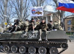 Men wearing military fatigues sit by a Russian flag and a white flag reading 'People's volunteer corps of Donetsk' as they ride on an armoured personnel carrier (APC) in the eastern Ukrainian city of Slavyansk on April 16, 2014. (GENYA SAVILOV/AFP/Getty Images)