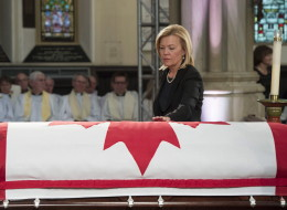 Christine Elliott touches the casket of her late husband at the state funeral for the Jim Flaherty in Toronto on Wednesday, April 16, 2014. THE CANADIAN PRESS/Frank Gunn