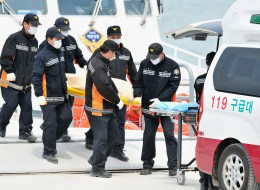 South Korean rescue members carry the body of a victim recovered from the 'Sewol' ferry to an ambulance at a harbour in Jindo on April 22, 2014.  (JUNG YEON-JE/AFP/Getty Images)