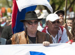 The Cowboy and Indian Alliance marches with rock icon Neil Young, center, to the National Museum of the American Indian in Washington, D.C., U.S., on Saturday, April 26, 2014. The Cowboy and Indian Alliance, along with leaders from Native American tribes like the Dene, Cree and Metis Peoples, presented a teepee to the museum to deliver to President Barack Obama in protest of the Keystone XL pipeline. Photographer Pete Marovich/Boomberg