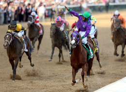 Jockey Victor Espinoza celebrates atop of California Chrome #5 after crossing the finish line to win the 140th running of the Kentucky Derby at Churchill Downs on May 3, 2014 in Louisville, Kentucky.  (Photo by Matthew Stockman/Getty Images)
