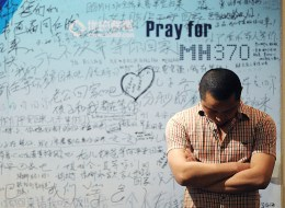 A man stands in front of a billboard in support of missing Malaysia Airlines flight MH370 as Chinese relatives of passengers on the missing Malaysia Airlines flight MH370 have a meeting at the Metro Park Hotel in Beijing on April 23, 2014. The hunt for physical evidence that the Malaysia Airlines jet crashed in the Indian Ocean more than three weeks ago has turned up nothing, despite a massive operation involving seven countries and repeated sightings of suspected debris..      AFP PHOTO / WANG