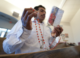 Delfino Velazquez holds his rosary beads as he prays with about 200 people who gathered for a prayer vigil at Saint Paul Catholic Church in Allentown, Pennsylvania.