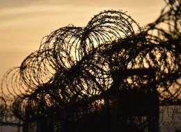This photo made during an escorted visit and reviewed by the US military, shows the razor wire-topped fence and a watch tower at the abandoned 'Camp X-Ray' detention facility at the US Naval Station in Guantanamo Bay, Cuba, April 9, 2014. AFP PHOTO/MLADEN ANTONOV        (Photo credit should read MLADEN ANTONOV/AFP/Getty Images)