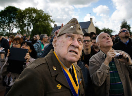World War II veteran Raymond W. Sylvester, 95, who was with the 86th Chemical Mortar Battalion while fighting in France, watches as paratroop veterans drop into Picauville during a ceremony honoring those who fought in the Normandy campaign on the day before the 70th anniversary of D-Day June 5, 2014 in Picauville, France. (Win McNamee/Getty Images)