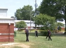 Officers case the grounds outside of the suspect's home, where a 3-year-old boy accidentally shot his brother.