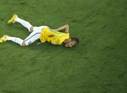 Brazil's forward Neymar reacts on the ground after being injured following a foul by Colombia's defender Juan Camilo Zuniga (unseen) during the quarter-final football match between Brazil and Colombia at the Castelao Stadium in Fortaleza during the 2014 FIFA World Cup on July 4, 2014. Brazil star Neymar was ruled out of the World Cup after that with a back injury, team doctor Rodrigo Lasmar said. Lasmar told reporters Neymar suffered a fracture in the third verterbra of his back during Brazil's