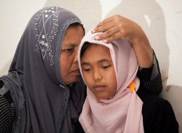 In this photograph taken on August 7, 2014, Indonesian mother Jamaliah (L) hugs her daughter Raudhatul Jannah (R) after they were reunited in Meulaboh, Aceh province. The Indonesian girl was swept away by the devastating 2004 tsunami and has been reunited with her family a decade after she was given up for dead, her mother said on August 8.  Jannah and her seven-year-old brother were carried off when huge waves struck their home in West Aceh district on December 26, 2004.       AFP PHOTO / CHAID