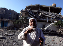 A Palestinian man reacts in front of the destroyed building after it was hit by an Israeli strike at the Jabalia region north of Gaza Strip on August 20, 2014. An extended ceasefire between the Palestinians and Israel expired at Tuesday midnight with violence flares up again after its ending. (Photo by Ashraf Amra/Anadolu Agency/Getty Images)