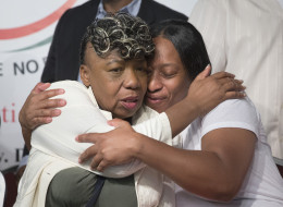Gwen Carr, mother of Eric Garner, left, and his sister Ellisha Garner, hug during a rally at the National Action Network headquarters, Saturday, July 26, 2014, in New York. (AP Photo/John Minchillo)