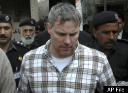 In this Friday, Jan. 28, 2011, photo, Pakistani security officials escort a U.S. consulate employee, identified as Raymond Davis, to a local court in Lahore, Pakistan. Colorado authorities say Davis, accused of shooting and killing two men while working as CIA contractor in Pakistan, faces misdemeanor charges after a fight Saturday, Oct. 1, 2011, over a shopping center parking spot in Highlands Ranch, Colo. In February, Davis shot two Pakistani men he said tried to rob him. Pakistan released him