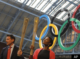Sebastian Coe, Chairman of the London Organizing Committee for the 2012 Olympic games, left, and former British athlete Denise Lewis hold up the relay torches as it is unveiled in central London, Wednesday, June, 8, 2011. The torch for the 2012 London Olympics has been revealed, a golden aluminum tube featuring a lace-like mesh with 8,000 holes that represent the number of bearers and how many miles it will travel in the 70-day relay across Britain. (AP Photo/Alastair Grant)